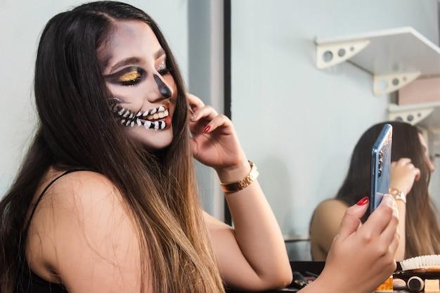 Belle fille avec du maquillage de crâne d'halloween prenant des selfies avec son téléphone intelligent dans sa chambre