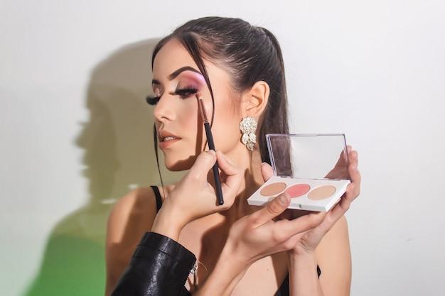 Belle fille avec du maquillage sur fond blanc. la maquilleuse applique un fard à paupières.
