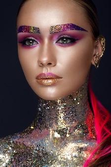 Belle fille avec du maquillage paillettes créatif, brille, sourcils inhabituels. la beauté est un visage d'art.