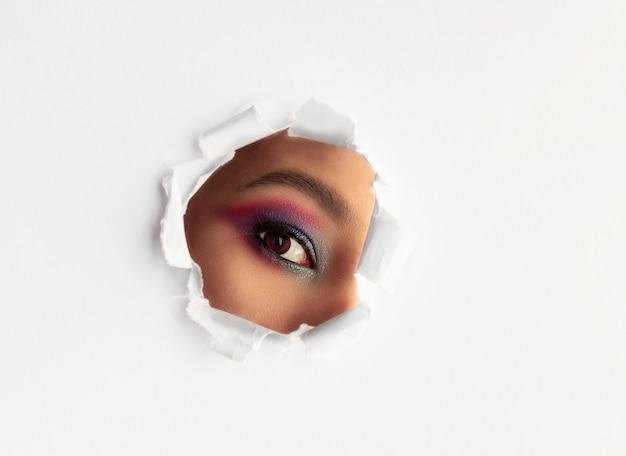 Belle fille avec du maquillage en regardant à travers un trou déchiré rond sur fond de papier blanc.