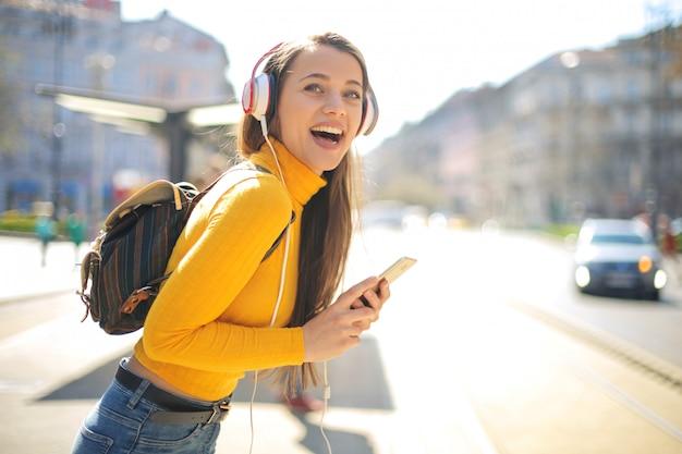 Belle fille écoute de la musique avec un casque tout en marchant dans la rue