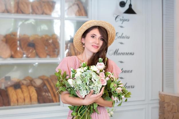 Belle fille élégante au chapeau de paille à l'intérieur d'une boulangerie française
