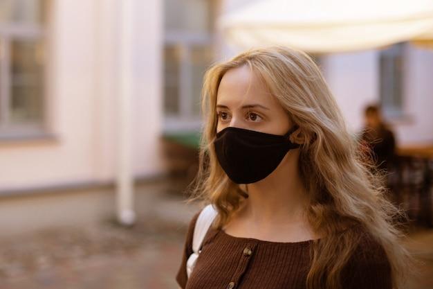 Belle fille élégante aux cheveux clairs dans un masque médical noir sur son visage
