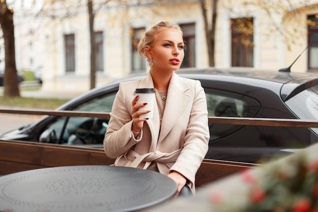 Belle fille élégante avec du café en manteau tendance automne se trouve à une table dans la rue