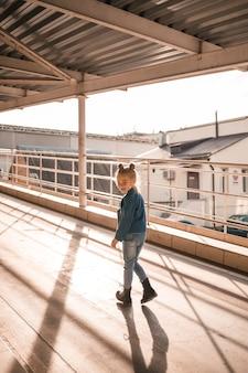 Belle fille élégante d'environ sept ans dans une veste en jean marche dans la rue