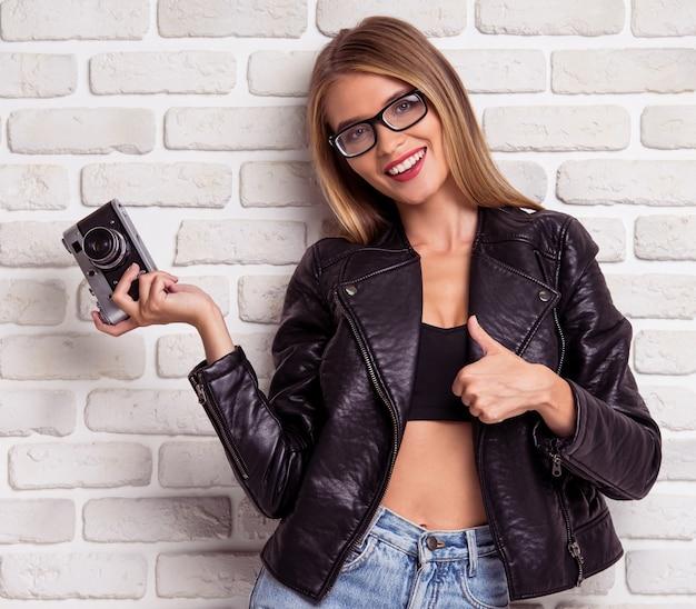 Belle fille élégante en jeans, veste en cuir noir.