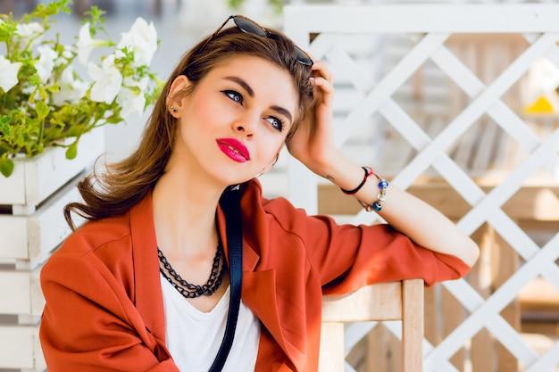 Belle fille élégante jeune amitié assis dans le restaurant d'été et rêver. bonne humeur de vacances d'été ensoleillées, couleurs vives. avoir des lèvres rouges pleines et de grands yeux bleus.