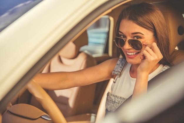 Belle fille élégante à lunettes de soleil au volant d'une voiture