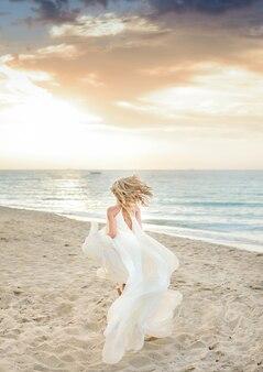 Belle fille élégante, posant au soleil sur la plage