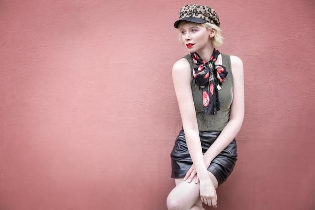 Belle fille élégante posant devant un mur rouge