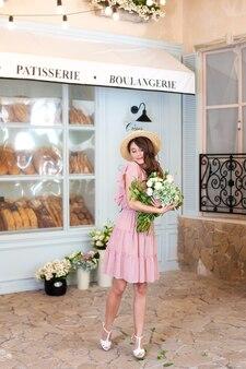 Belle fille élégante en robe et chapeau de paille avec bouquet de fleurs en boulangerie française
