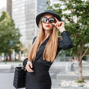 Belle fille élégante en vêtements noirs avec des lunettes de soleil