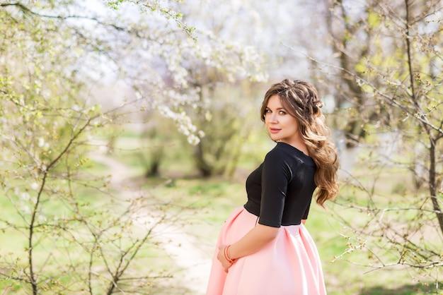 Belle fille enceinte dans le jardin de printemps
