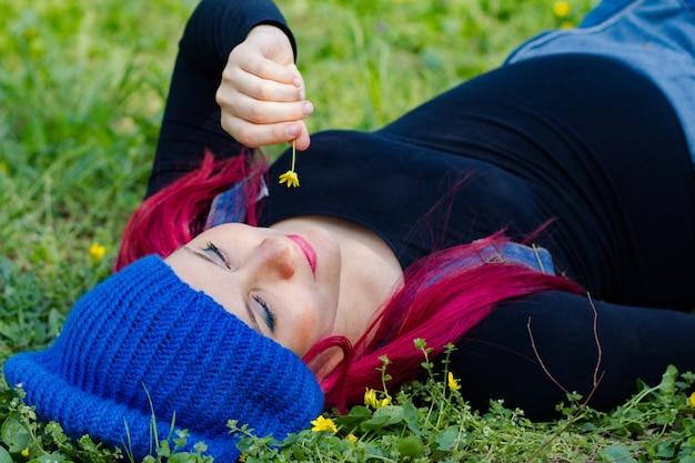 Belle fille enceinte lumineuse se promène dans le parc de printemps de floraison
