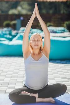 Belle fille enceinte en position du lotus avec les mains levées à l'air frais