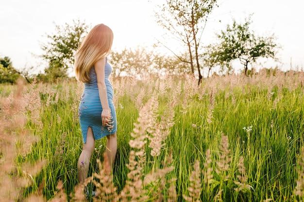 Belle fille enceinte en robe d'été élégante courir, aller marcher dans le champ avec des fleurs au soleil, profiter du sentiment de liberté