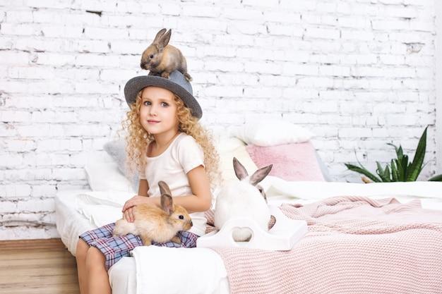 Belle fille enfant aux cheveux bouclés et animaux lapins moelleux assis sur un chapeau