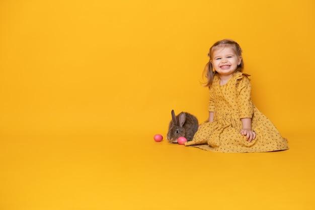 Belle fille enfant en robe jaune assis avec lapin et oeufs colorés sur fond jaune.
