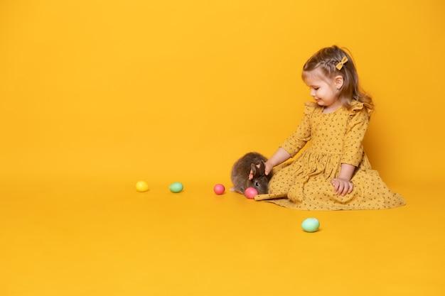 Belle fille enfant en robe jaune assis avec lapin et oeufs colorés.
