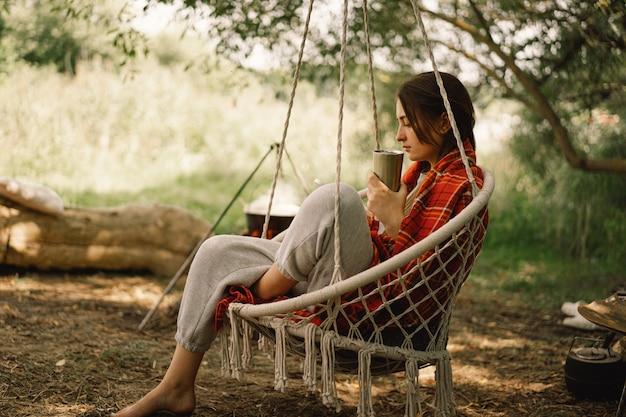 Belle fille enveloppée dans un plaid rouge buvant du thé dans une chaise suspendue confortable voyage d'aventure en plein air