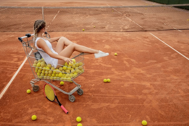 Belle fille est assise dans le panier de balles de tennis tout en tenant des balles de tennis et une raquette dans sa main.