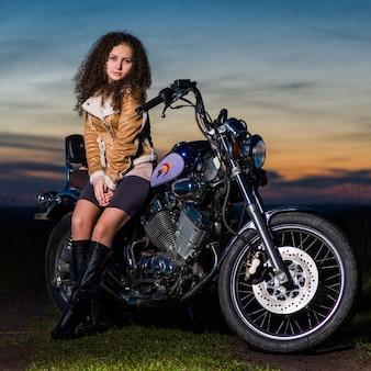 Belle fille est assise sur une moto le soir