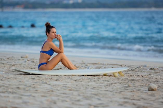 Belle fille est assise sur la plage avec une planche de surf.