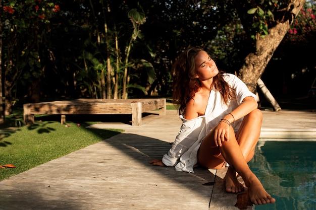 Belle fille est assise près de la piscine.