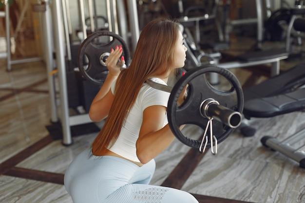 Une belle fille est engagée dans une salle de sport avec un haltère