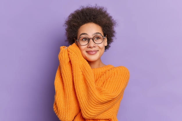 Belle fille ethnique aux cheveux afro naturels garde les mains près du visage et regarde quelque part avec une expression de rêve porte un pull en tricot orange ample.