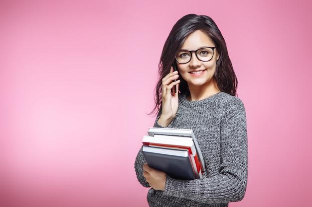 Belle fille étudiante avec des livres parler au téléphone sur fond rose