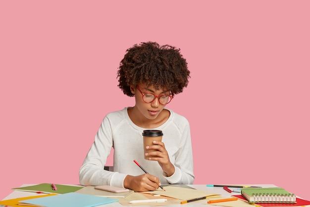 Belle fille étudiante posant au bureau contre le mur rose
