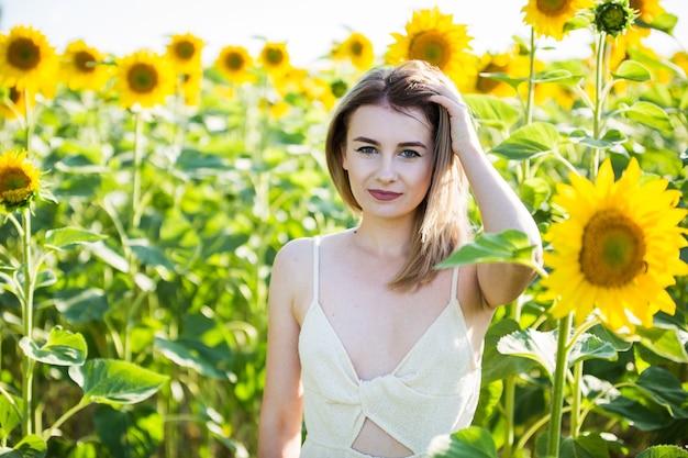 Belle fille européenne dans une robe blanche sur la nature avec des tournesols