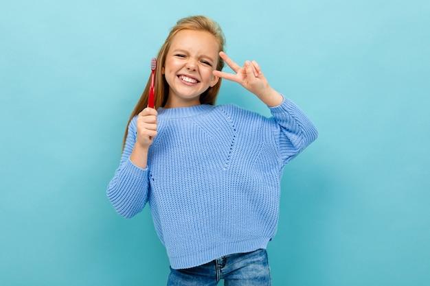 Belle fille européenne tenant une brosse à dents dans ses mains sur bleu clair