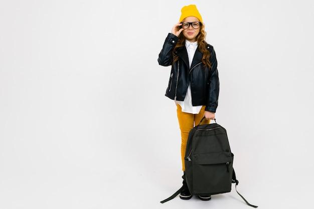 Belle fille européenne vêtue d'un chapeau jaune, des lunettes et une veste en cuir avec un sac à dos à la main en pleine croissance sur blanc