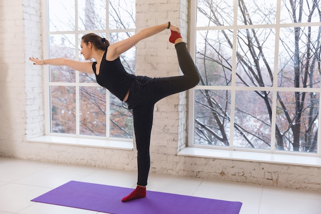 Belle fille faisant du yoga pose à gauche debout sur le sol en face de la fenêtre dans une pièce lumineuse.
