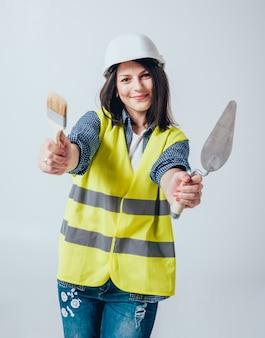 La belle fille fait des réparations dans leur maison.