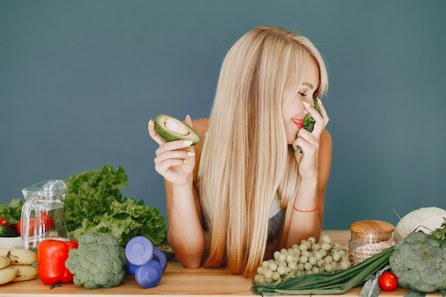 Belle fille fait une salade. blonde sportive dans une cuisine. femme à l'avocat.