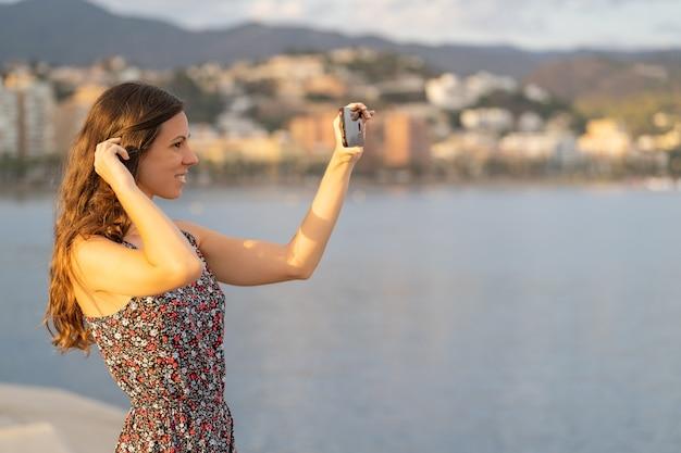 Belle fille fixe ses longs cheveux à l'aide de l'appareil photo de son smartphone