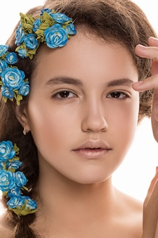 Belle fille avec des fleurs dans les cheveux, une peau parfaite. concept - soins personnels