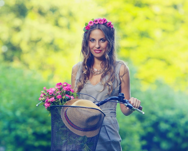 Belle fille avec des fleurs sur un vélo