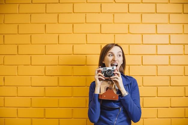 Belle fille folle avec appareil photo argentique rétro sur mur de briques de fond jaune.