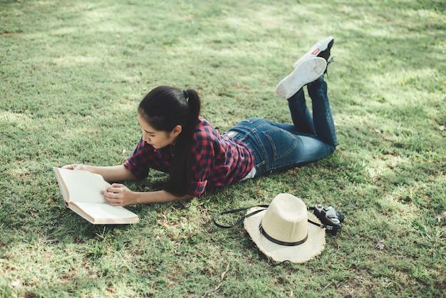 Belle fille en forêt d'automne en lisant un livre