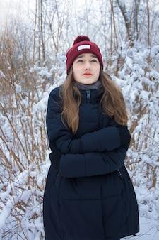 Belle fille gelant dans la forêt d'hiver. portrait de sérieuse jolie jeune adolescente aux longs cheveux blonds aux yeux verts sur fond violet bleu flou naturel dans la forêt enneigée givrée