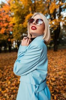 Belle fille glamour avec des lunettes de soleil à la mode et des lèvres rouges dans un manteau bleu vif se promène dans un parc d'automne au feuillage jaune
