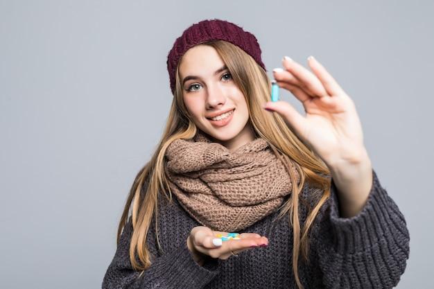 Belle fille avec la grippe ou le rhume a beaucoup de médicaments à prendre pour devenir en bonne santé sur le gris