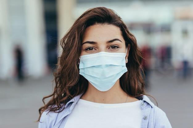 Belle fille avec une grosse valise à l'aéroport portant un masque de protection sur son visage