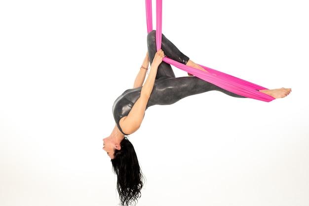 Belle fille gymnaste fait voler le yoga sur un hamac rose