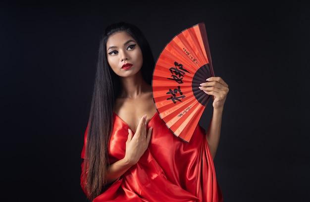 Belle fille habillée en geisha dans un kimono rouge avec un ventilateur
