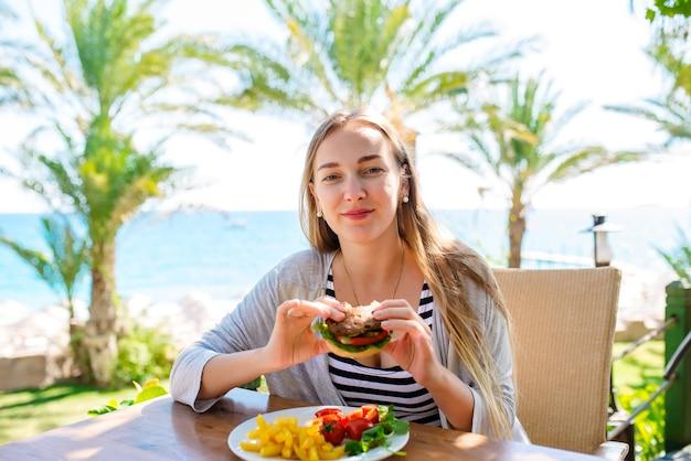 Belle fille a un hamburger en vacances à la mer.